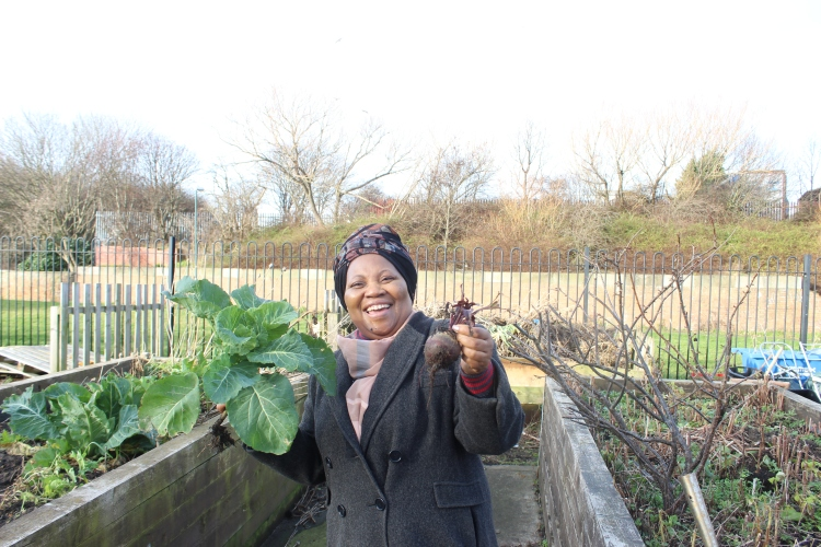 A black woman in a grey coat and black floral headdress is smiling and holding vegetables up to the camera. She is surrounded by vegetable patches.